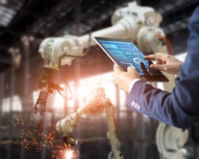 Mann steuert Roboter mit Tablet