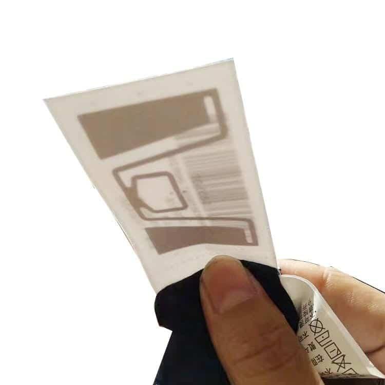 rfid-Kleidungsanhänger in der Hand mit durchscheinender Chip-Antenne bei Sonnenlicht