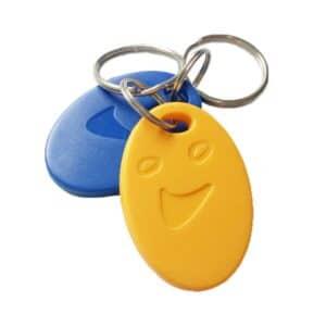 zwei RFID/NFC-Schlüsselanhänger in gelb und blau mit Smiley-Form
