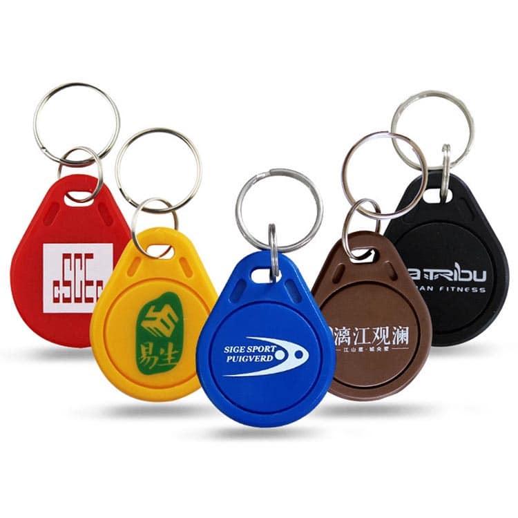 verschiedene ABS RFID Schlüsselanhänger in den Farben rot, gelb, blau, braun und schwarz mit Logodruck in weiß