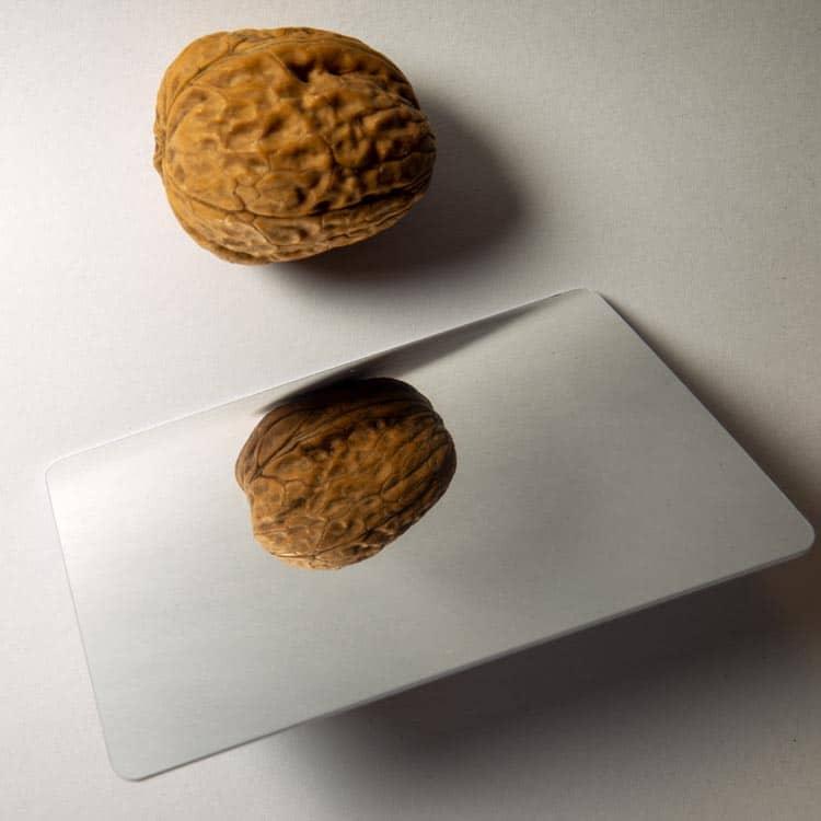 RFID-Chipkarte mit Spiegelfläche neben einer Baumnuss